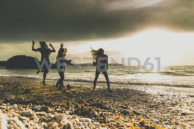 Excited friends on the beach at sunset - UUF11647