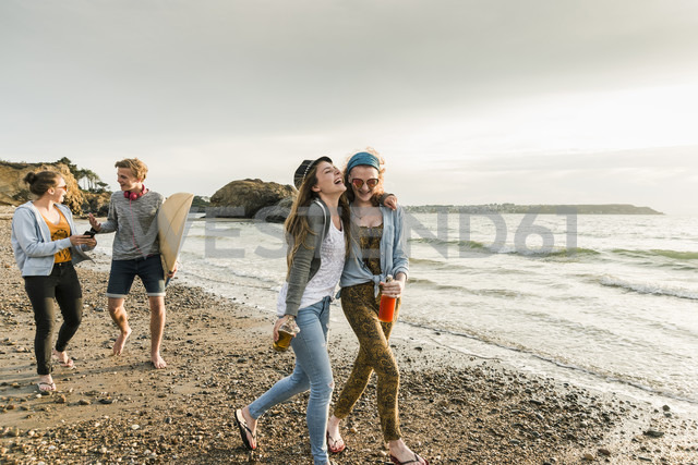 Happy friends with surfboard and drinks walking on stony beach - UUF11653