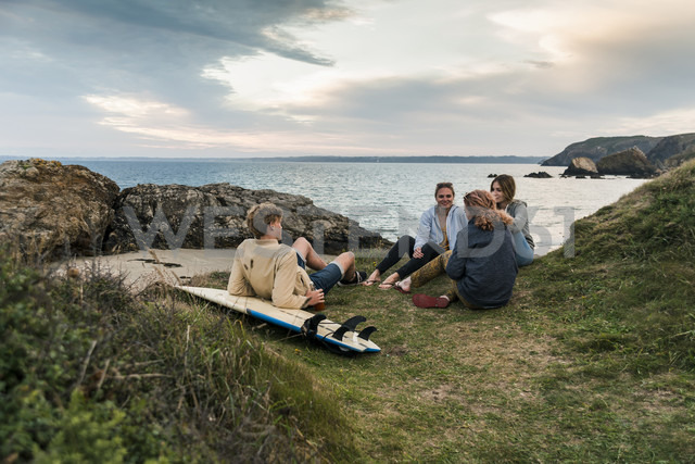 Happy friends with surfboard socializing at the coast at sunset - UUF11674