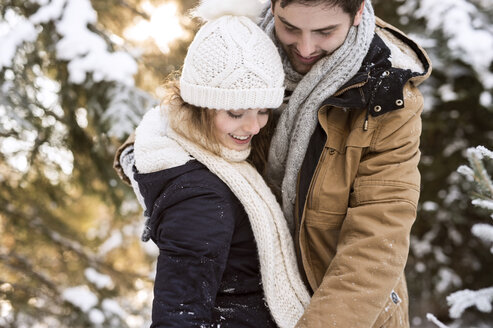 Happy young couple in snow-covered winter forest - HAPF02021