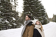 Happy young couple standing back to back in snow-covered winter landscape - HAPF02033