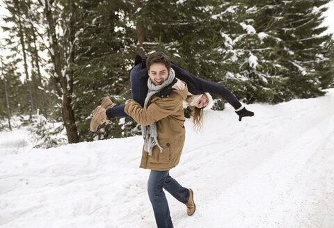Happy young couple having fun in snow-covered winter landscape - HAPF02036