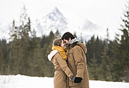 Happy young couple standing head to head in winter landscape - HAPF02042