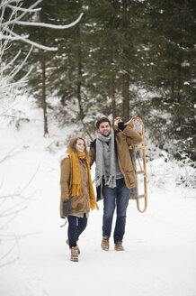 Happy young couple with sledge in winter forest - HAPF02045