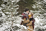 Happy young couple wrapped in blanket standing in winter forest - HAPF02048