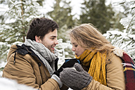 Young couple in love with cups of tea in winter forest - HAPF02051