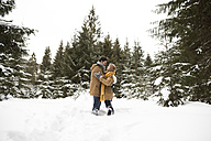 Happy young couple standing face to face in winter landscape - HAPF02054