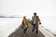 Young couple in love walking on empty country road in snow-covered landscape - HAPF02057