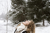 Happy young woman enjoying snowfall in winter forest - HAPF02072