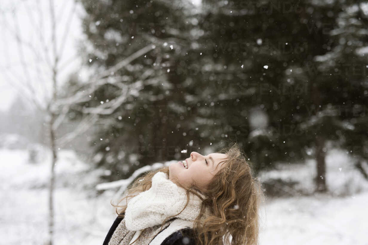 Happy young woman enjoying snowfall in winter forest - HAPF02072 - HalfPoint/Westend61