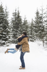 Happy young couple having fun in snow-covered winter forest - HAPF02075
