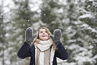 Portrait of happy young woman at snowfall in nature - HAPF02078