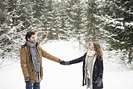 Happy young couple standing hand in hand in winter landscapelooking at each other - HAPF02081
