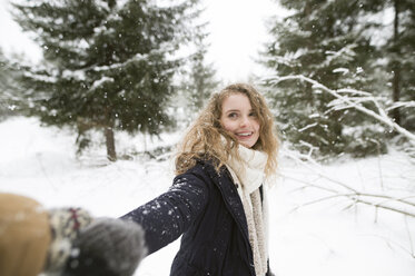 Portrait of happy young woman holding hand in winter forest - HAPF02084