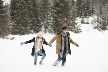 Happy young couple walking in snow-covered winter landscape - HAPF02093