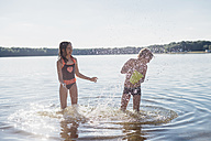 Boy and girl splashing with water at lakeshore - MJF02178
