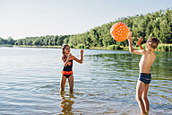 Boy and girl standing at lakeshore playing with beach ball - MJF02181