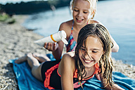 Portrait of laughing girl on the beach with her friend - MJF02193