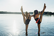 Back view of two friends doing stretching exercise at lakeshore - MJF02199