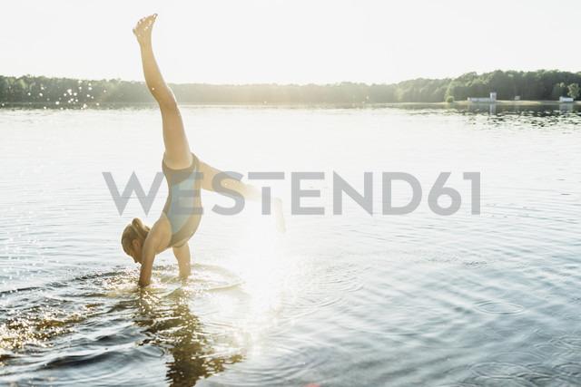 Girl doing cartwheel at lakeshore - MJF02202