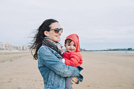 Portrait of smiling baby girl on her mother's arms on the beach - GEMF01774