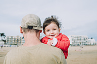 Portrait of smiling baby girl on her father's arms on the beach - GEMF01777