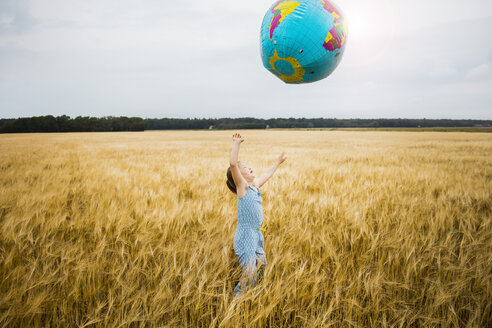 Girl standing in grain field playing with globe - MOEF00076
