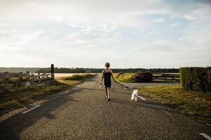 Girl walking with dog on rural road holding miniature wind turbine - MOEF00094