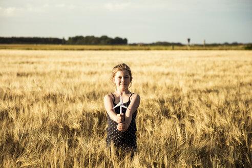 Girl standing in grain field holding miniature wind turbine - MOEF00097