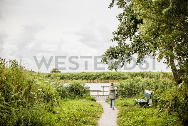 Girl walking on path towards lake - MOEF00103