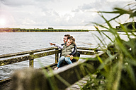 Mother and daughter on jetty at a lake - MOEF00106