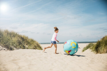 Girl playing with globe on the beach - MOEF00121