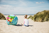 Girl with globe on the beach - MOEF00124