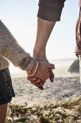 Portugal, Algarve, close-up of couple holding hands at sunset on the beach - JRF00331