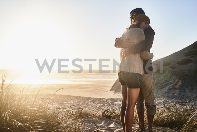 Portugal, Algarve, couple hugging at sunset on the beach - JRF00337