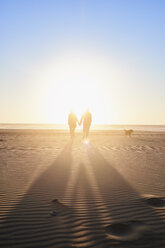 Portugal, Algarve, couple with dog walking on the beach at sunset - JRF00340