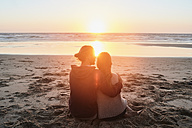 Portugal, Algarve, couple sitting on the beach at sunset - JRF00346