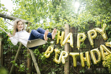 Portrait of swinging girl in garden with decoration for Birthday Party in the background - MOEF00135