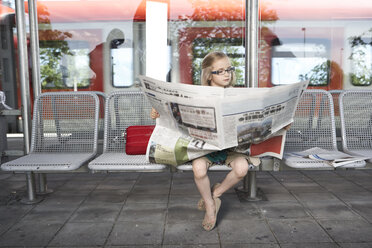 Portrait of little girl sitting at platform reading newspaper - FSF00947