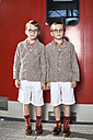Twin brothers standing in front of commuter line - FSF00953