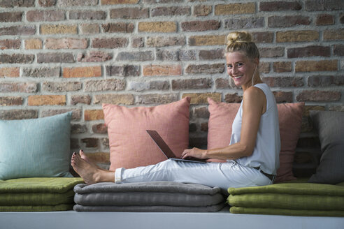 Mature woman sitting on couch, usine laptop - RIBF00676