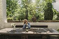 Mature woman sitting on terrace, enjoying summer - RIBF00679