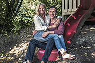 Happy couple sitting on slide of garden shed in the woods - RIBF00685