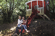 Happy couple sitting on slide of garden shed in the woods - RIBF00688