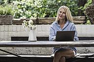 Mature woman sitting on terrace, using laptop - RIBF00712