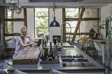 Woman sitting in kitchen, using laptop - RIBF00721