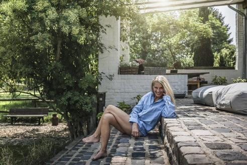 Mature woman sitting on terrace steps - RIBF00724