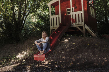 Mature woman sitting on slide in front of garden shed in the woods - RIBF00745