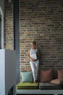 Mature woman standing on couch, holding laptop - RIBF00754
