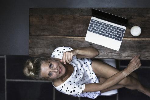 Woman sitting in kitchen, using laptop - RIBF00760